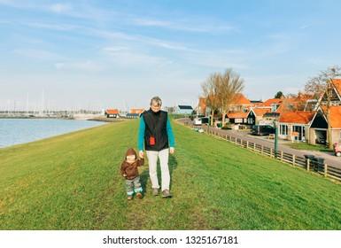 Man with toddler walking on dyke – Hindeloopen, Netherlands, Europe