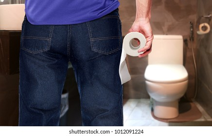 Man in a toilet holding tissue roll