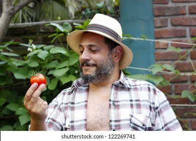 man with tomato in the garden