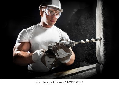 Man with a tool. Worker using a drilling power tool on construction site. Young man using electric drill on white brick wall in a white helmet.