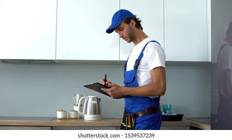 Man with tools writing report inspecting kitchen on electrical safety, service