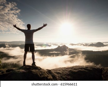 Man at the top of a mountain looking the misty landscape around. Feel free