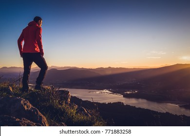 A man at the top of a mountain, outdoors, enjoying the landscape at sunrise.