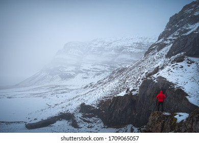 A man at the top of a rock in a full of snow landscape in Iceland.
