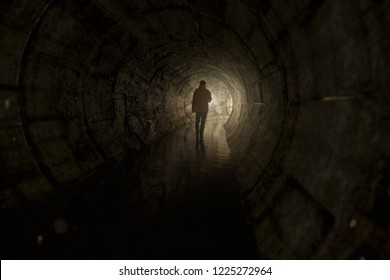 Man with a torch walks through a tunnel