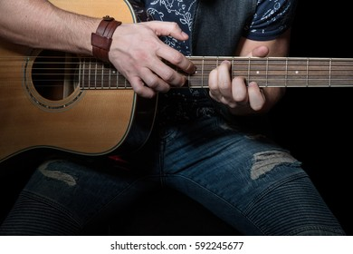 Man in torn jeans delicately playing an acoustic guitar, close-up, on a black background