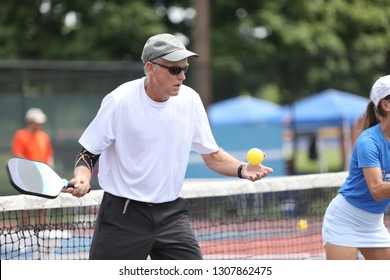 A man tosses a ball to start a serve, competing in a pickleball tournament