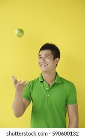 Man tossing green apple