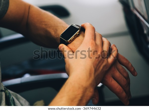 Man touch his smart watch on hand in aircraft