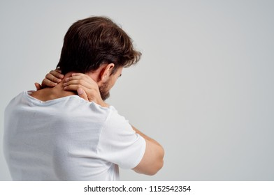 man touches his neck with his hands, rear view