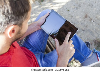 Man touching an electronic tablet while sitting in a bench.