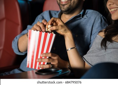 Man touching the hand of his date while grabbing some popcorn at the movie theater