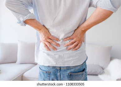 Man is touching his back because it aches. Backache concept bending over in pain with hands holding lower back. Close up of man rubbing his painful back. Pain relief, chiropractic concept
