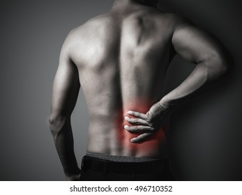 Man is touching his back because it aches,monochrome photo with red as a symbol for the hardening