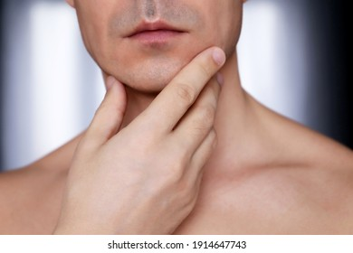Man touching his shaved chin, beauty and skin care concept. Male face and neck close up