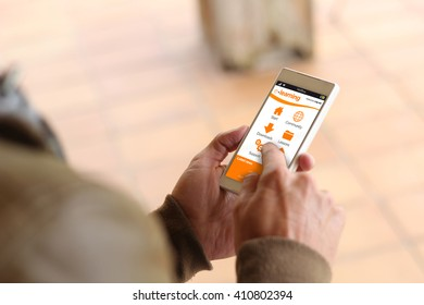 man touching the screen of his smartphone at street showing elearning. All screen graphics are made up.