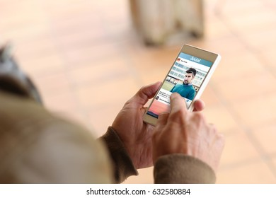man touching the screen of his smartphone to check social photo network. All screen graphics are made up.