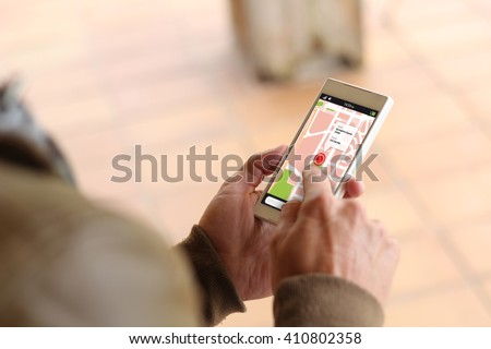 man touching the screen of his smartphone showing gps app. All screen graphics are made up.
