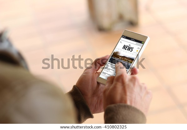 man touching the screen of his smartphone showing news website. All screen graphics are made up.