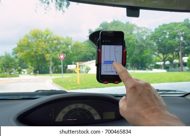 A man is touching the screen on his smartphone cellphone that is in a holder cradle mount on the inside of the windshield in car.