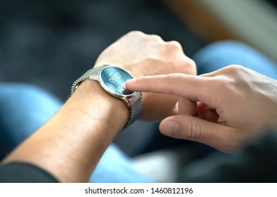 Man touching smart watch screen to open notification and read message. Wearable hybrid mobile device, gadget and activity tracker in wrist. Wearing digital smartwatch in hand. People with wearables.