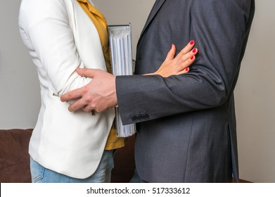 Man touching woman's elbow - sexual harassment in business office
