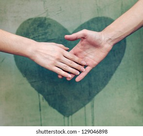 Man touching woman's hand with a heart painted wall in background