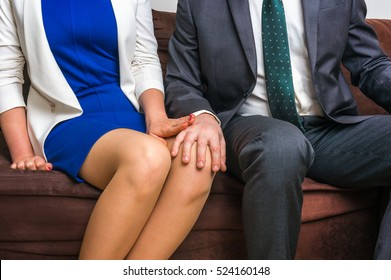 Man touching woman's knee - sexual harassment in business office