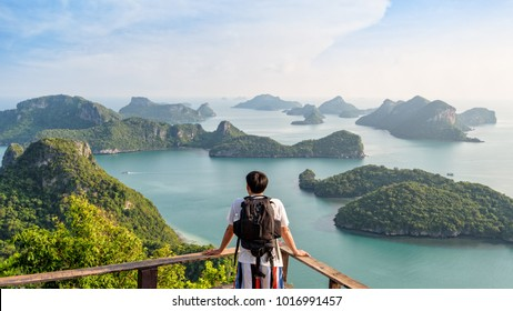 Man tourist with backpack are looking at the beautiful natural landscape of the sea on peak view point of Ko Wua Ta Lap island in Mu Ko Ang Thong National Park, Surat Thani, Thailand, 16:9 Widescreen