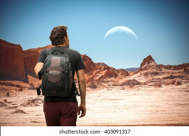man tourist with a backpack. The moon in the Moon Valley in Atacama Desert, Chile