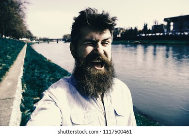 Man, tourist with beard and mustache on cheerful, smiling face, riverside background. Hipster, tourist with tousled hair and long beard looking at camera, taking selfie photo. Selfie photo concept.