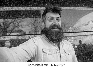 Man, tourist with beard and mustache on cheerful, smiling face, black marble background. Selfie photo concept. Hipster, tourist with tousled hair and long beard looking at camera, taking selfie photo.
