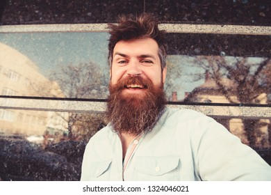 Man, tourist with beard and mustache on cheerful, smiling face, black marble background. Vlogging concept. Hipster, tourist with tousled hair and long beard looking at camera, taking selfie photo.