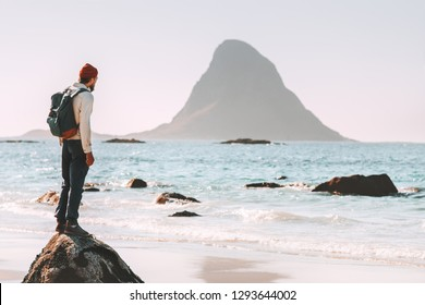 Man tourist enjoying sea and rock view on beach summer traveling in Norway  vacations outdoor lifestyle adventure trip escape solitude emotions