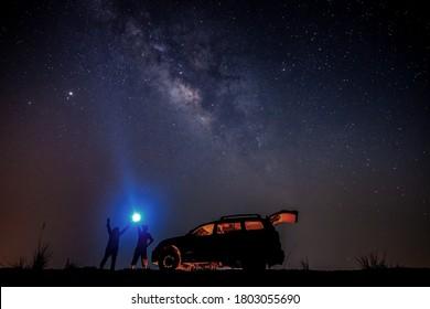 Ein Tourist mit Taschenlampe in der Nähe seines Campingwagens in der Nacht. Weltraumhintergrund mit Lärm und Korn. Nachtlandschaft mit dem Auto und bunt leuchtend milchig.Schöne Szene mit dem Universum.