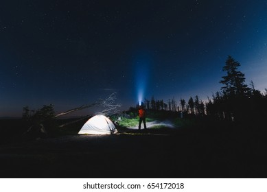 Man tourist with flashlight near his camp tent at night. Malinowska Skala. Szczyrk. Silesian Beskid, Poland