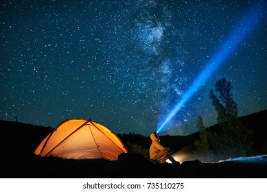 Man tourist with flashlight near his camp tent at night under a sky full of stars. Orange illuminated tent.