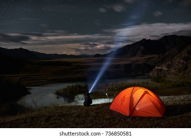 Man tourist with flashlight near his camp tent at night. Orange illuminated tent.