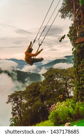 Man tourist having fun swinging on Giant Swing in Casa del Arbol attraction. View of green mountains and trees in background. Wooden Treehouse. Shot in Banos, Ecuador