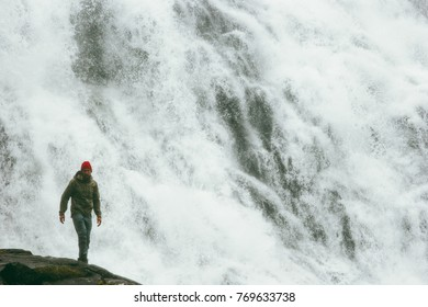 Man tourist hiking at big waterfall outdoor Travel Lifestyle success concept adventure scandinavian vacations in Norway wild nature