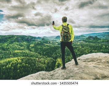Man tourist hiking mountain trail, takes picture by phone. Hiker walking on rocky hill, wearing backpack and sunglasses, using trekking sticks