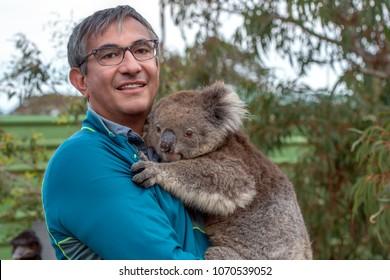 Man tourist and koala in australia kangaroo island while holding