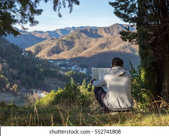 Man tourist in mountain read the map sitting on grass. Man on top of mountain under a tree shadow. Tourism concept
