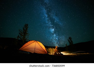 Man Tourist Near His Camp Tent At Night Under A Sky Full Of Stars Orange