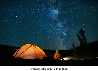 Man tourist near his camp tent at night under a sky full of stars. Orange illuminated tent.