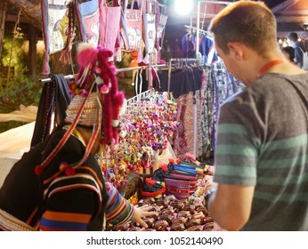 A man, tourist, negotiating the price of hill tribe souvenirs in Chiang Mai, Thailand - bargaining skill