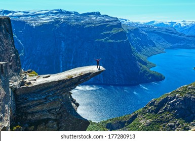 Man tourist on summer Trolltunga (The Troll's tongue) in Odda ( Ringedalsvatnet lake, Norway). Beautiful natural vacation hiking walking travel to nature destinations concept.