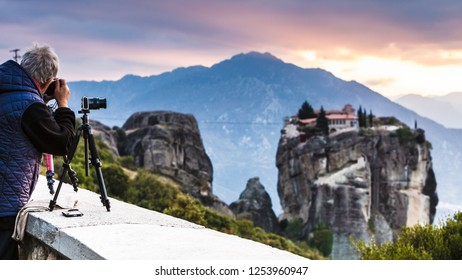 Man tourist with professional camera on tripod taking picture film video from the Holy Trinity Monastery at sunset. The Meteora monasteries, Greece Kalambaka.