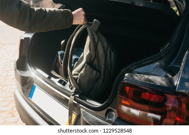A man or a tourist puts a backpack in the trunk of a car. Preparation for the trip. The concept of tourism or travel by car.