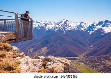 A man tourist stands on viewpoint above  valley against mountains covered with  snow. A man looks at beautiful panorama of the mountains. National Park Peaks of Europe. Cantabria, Spain, Europe